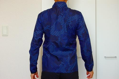 アシックス グラフィックウーブンジャケットを着た背面イメージ